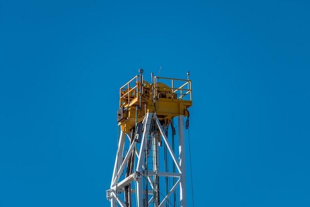 青空を背景にした掘削塔の上部。