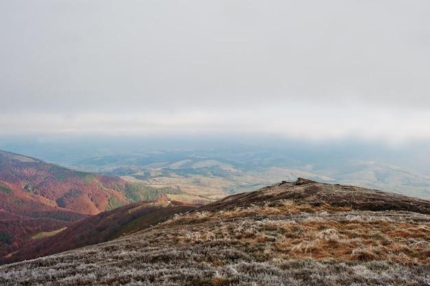 Верхняя часть холма горы заморозка на холме леса предпосылки осени прикарпатских гор красном. встреча осени и зимы на природе.