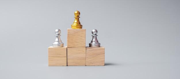 Вершина золотых шахматных пешек или лидера бизнесмена. победа, лидерство, успех в бизнесе, команда, подбор персонала и концепция совместной работы