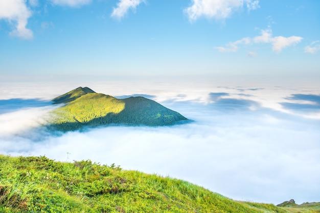 Вершина зеленой горы в облаках