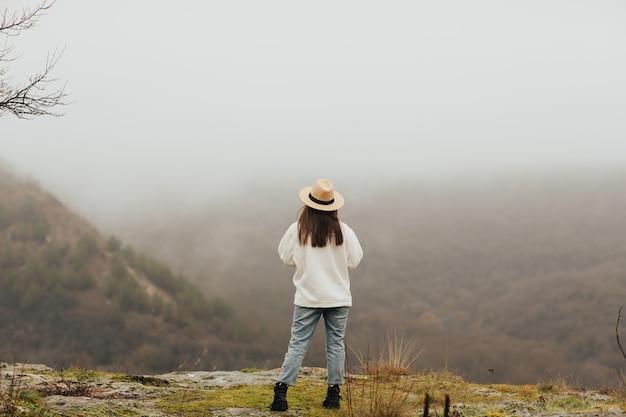 겨울에 안개와 산 골짜기의 정상입니다. 소녀는 안개 낀 아침에 산으로 긴장을 풀고 있습니다.
