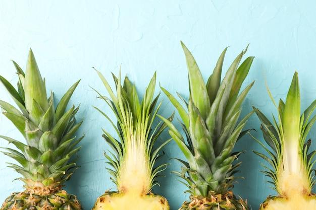 青色の背景にパイナップルの上部をクローズアップ。ジューシーなフルーツ