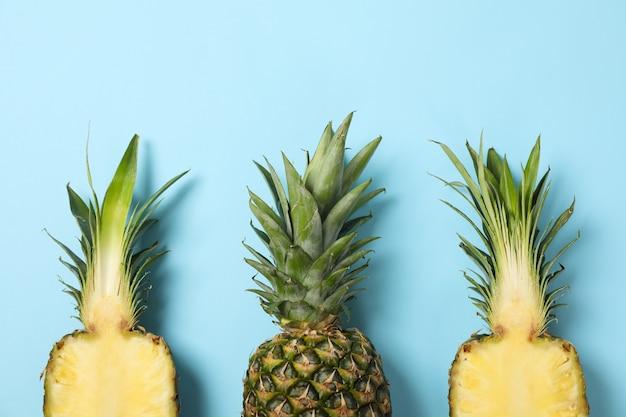 Верхняя часть ананасов на голубой предпосылке, взгляд сверху. сочные фрукты