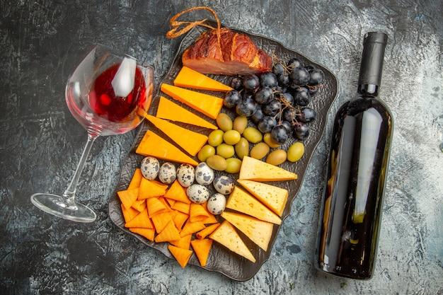 茶色のトレイと落ちたワイングラスと氷の背景の上のボトルのおいしい最高のスナックのトップ