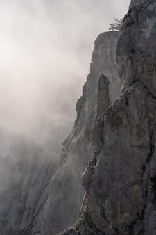 山の頂上。日没時に霧の中の高い岩。カラフルな自然の背景。
