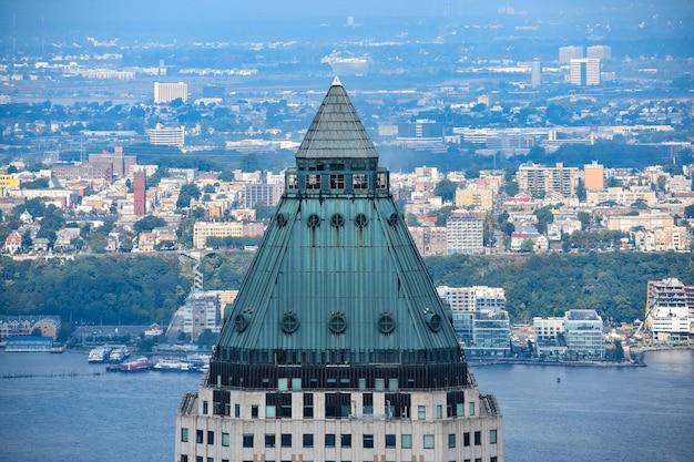 Верхняя часть башни с металлической крышей и нью-джерси-сити и рекой гудзон на заднем плане. манхэттен, нью-йорк. сша.