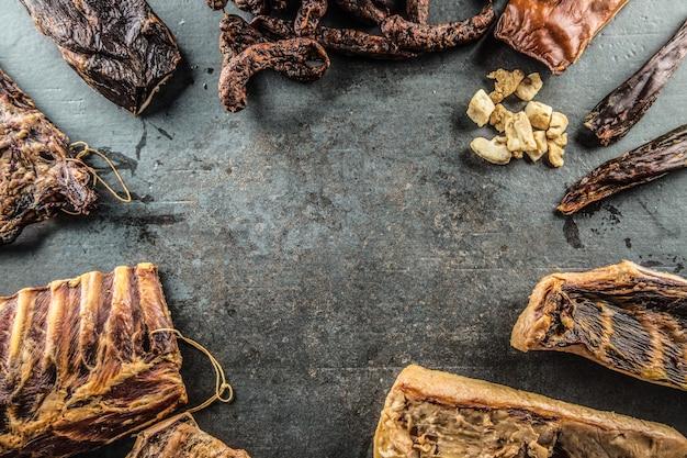 Вид сверху на ассортимент копченостей из свинины - колбасы, ребрышки из бекона и др.
