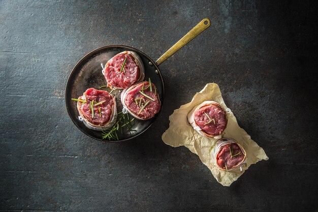 ベーコンに包まれた牛ヒレ肉のステーキを鍋に入れて保存。