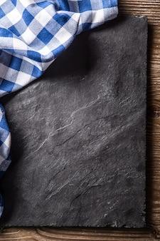 黒のスレートボード上のビューの青い市松模様のテーブルクロスの上面。
