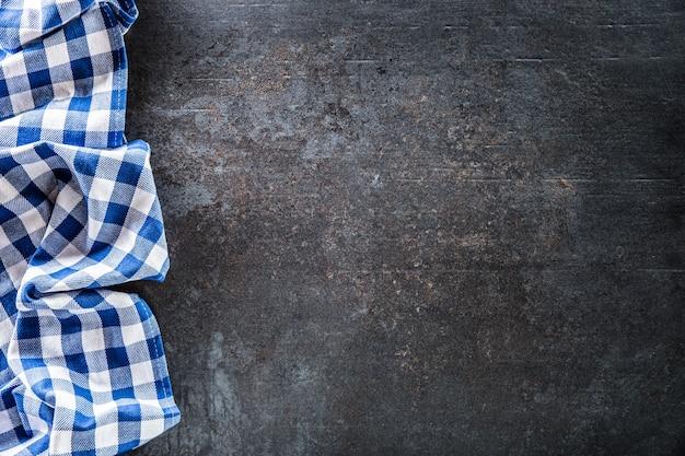 어두운 콘크리트 테이블에 파란색 체크무늬 식탁보가 맨 위에 있습니다.