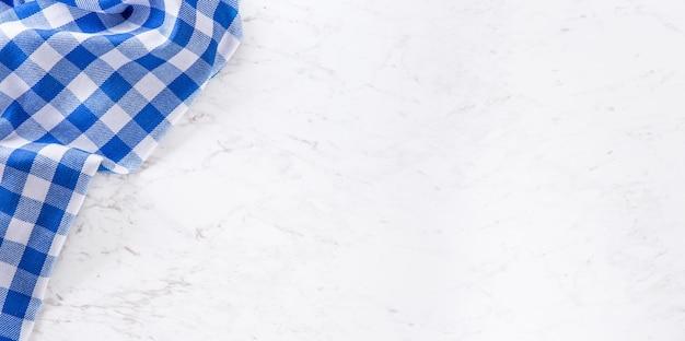 흰색 대리석 테이블에 파란색 체크 무늬 식탁보가 맨 위에 있습니다.
