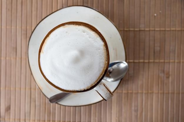 テーブルの上のビューカプチーノコーヒー、白い泡に焦点を当てる