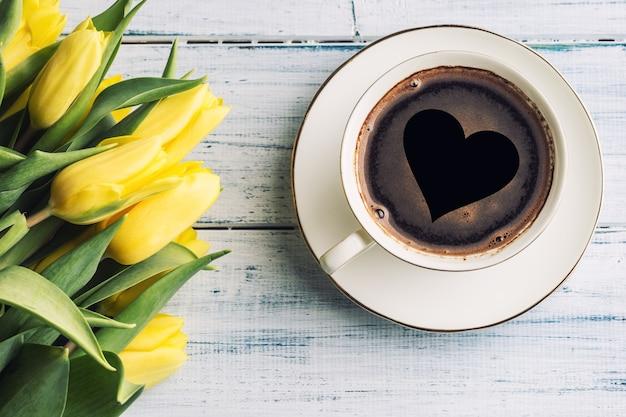 Верхняя часть кофе формы чашки взгляда с тюльпанами сердца и весны на деревянном столе взгляд сверху.