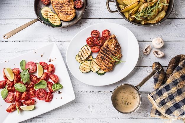 Обеденный стол сверху с жареной куриной грудкой, салатом из жареных овощей и грибным соусом