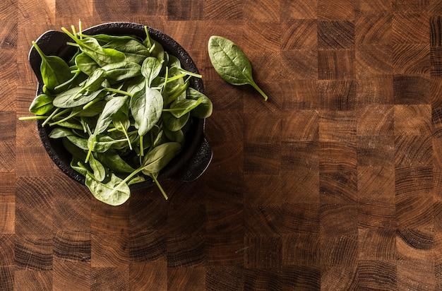 ビューのトップビュー新鮮なほうれん草の葉は肉屋のボード上のボウルに。