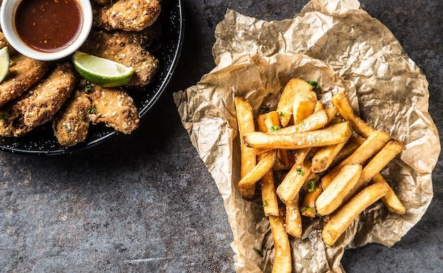맨 위에 프라이드 치킨 윙 칠리 소스 라임과 감자 튀김이 있습니다.