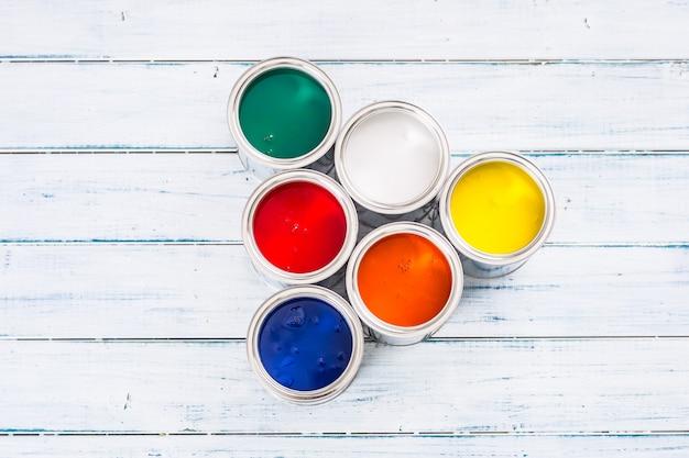 탁자 위에 여러 가지 빛깔의 페인트 캔으로 가득 찬 상단.