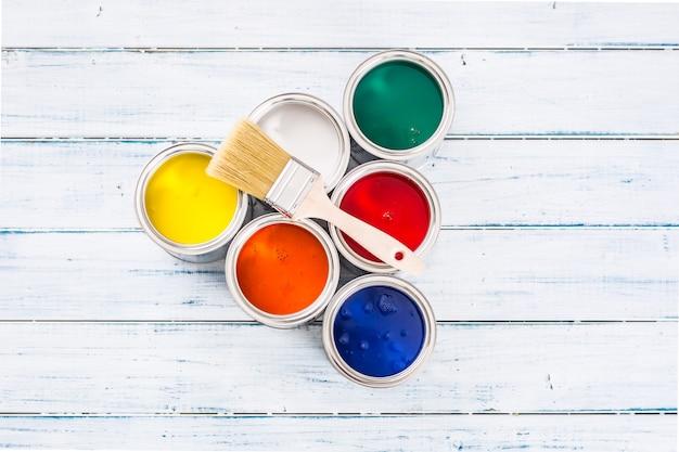 탁자에 브러시가 있는 여러 가지 빛깔의 페인트 캔으로 가득 찬 상단.