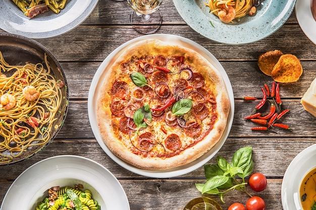 プレートとフライパンでのイタリア料理のフルテーブルのトップビュー。ピザパスタのリゾットスープと魚の野菜サラダ。