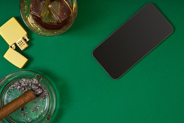 緑のポーカーテーブルのウイスキーグラスの近くの灰皿に葉巻のビューの上面。コピースペースを使用して上から表示します。オンラインカジノのバナーテンプレートレイアウトモックアップ。緑のテーブル、職場の上面図。