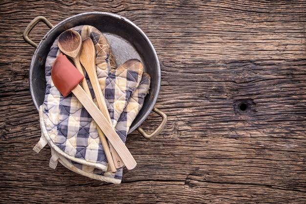 Вид сверху на винтажную кухонную утварь на деревенском деревянном фоне.