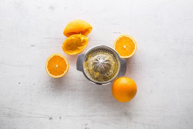 위쪽 보기 오렌지와 흰색 콘크리트 배경에 과즙 짜는기구.