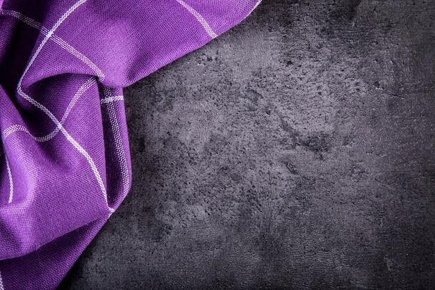 暗いキッチンのコンクリートテーブルに紫色の市松模様のナプキンを表示します。