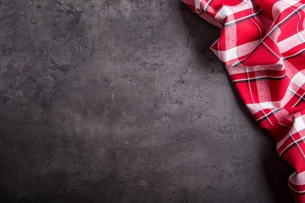 暗いキッチンのコンクリートテーブルの上のビューの赤い市松模様のナプキン。
