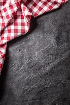 黒のスレートボード上のビューの上部の赤い市松模様のテーブルクロス。