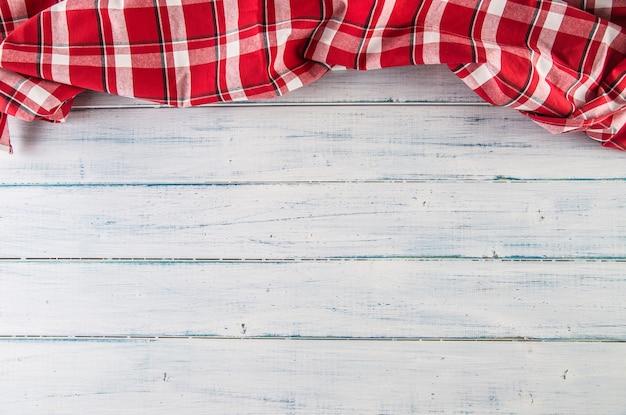 木製のテーブルの上のビューの赤い市松模様のテーブルクロス。