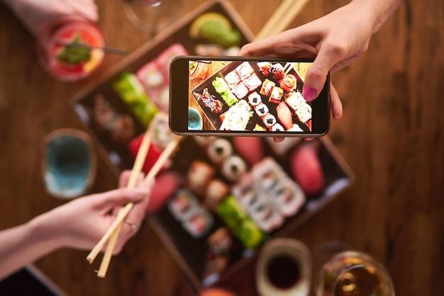 보기의 상단. 두 소녀가 초밥을 먹고 스마트 폰으로 사진을 찍습니다. 음료와 함께 다양한 종류의 롤과 초밥 세트