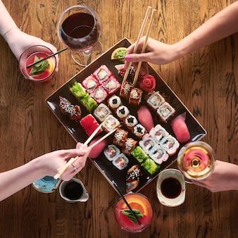Вид сверху. две девушки едят суши. набор различных видов роллов и суши с напитками