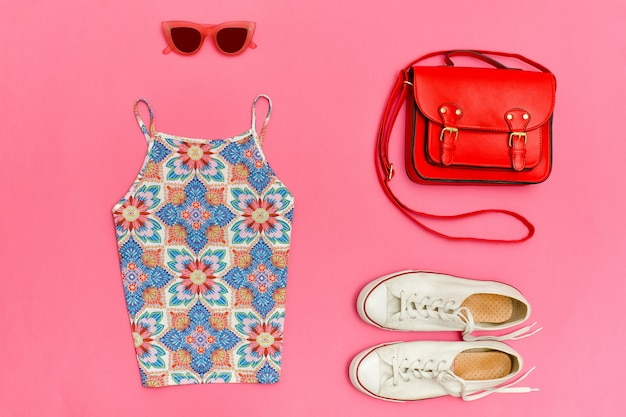 Top in ornament, red handbag, white sneakers and rose colored glasses bright pink background, close up