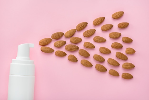 Top above overhead cropped close up view photo of bottle spreading almond nuts to the side isolated over pastel color background copy empty blank space