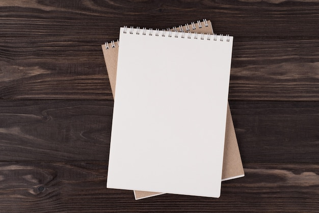 Top above overhead view flat lay photo of a blank notebook isolated on wooden background with copyspace