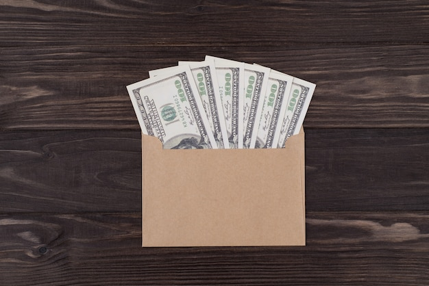 Top above overhead view flat lay photo of craft envelope full of dollars isolated on wooden background with copyspace