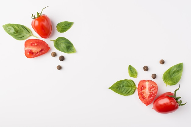 Top above overhead view photo of of cherry tomatoes surrounded with peppercorns and basil leaves placed in corners isolated on white background