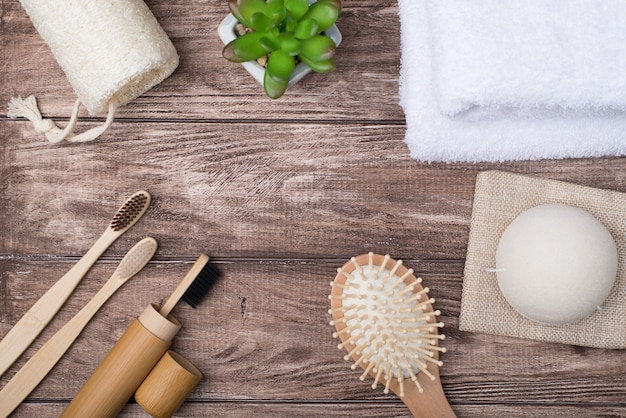Top above overhead view photo of eco bath products supplies and a succulent isolated on wooden background making center empty
