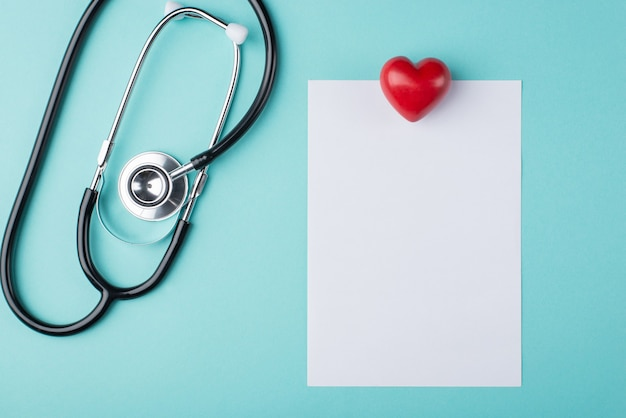 Top above overhead view photo of medical prescription paper with stethoscope beside and a heart isolated on turquoise background