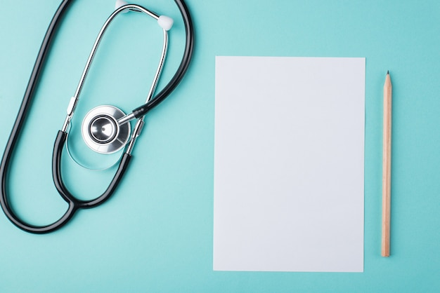 Top above overhead view photo of medical prescription paper with stethoscope beside isolated on turquoise background