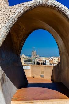 アントニオガウディによって設計されたカサミラ(カサミラとも呼ばれます)の屋根からのバルセロナの風景のトップパノラマビュー。ヨーロッパ、バルセロナ、スペイン。背景にサグラダファミリア。