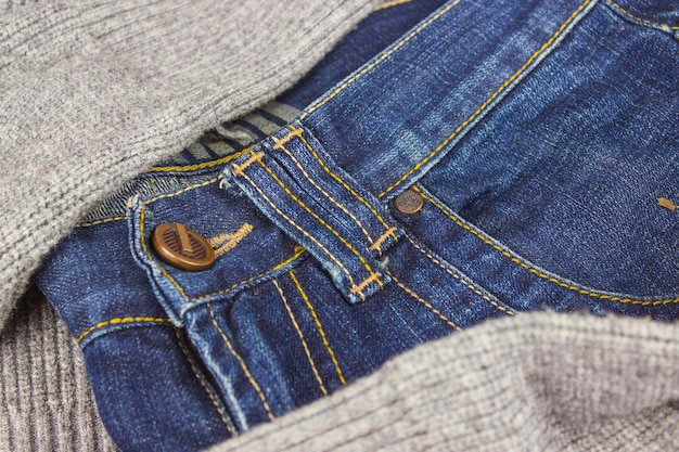The top part of jeans. front part of the jeans on sweater background, close-up.