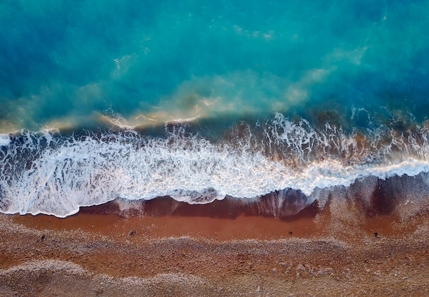 Top photo view from flying drone of tropical coral sea landscape with turquoise water and waves approaching the beach.