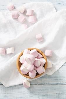 ピンクと白のマシュマロでいっぱいの木製のボウルの上面の縦向きのビュー。白いテーブルクロスの上にいくつかが散らばっています。