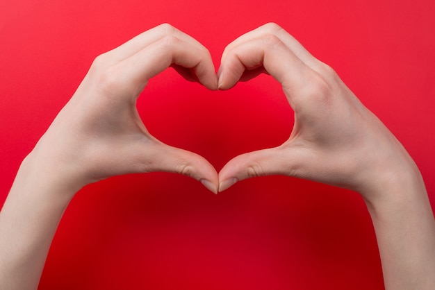 Top pov above overhead close up view photo of woman making heart with her hands isolated on red background