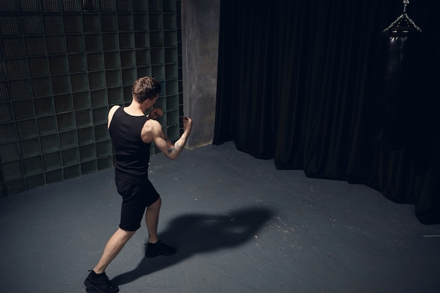 Top rear view of athletic fir young man with muscular arms wearing black clothes while boxing, punching invisible enemy, standing isolated in dark room, casting shadow on gray concrete floor