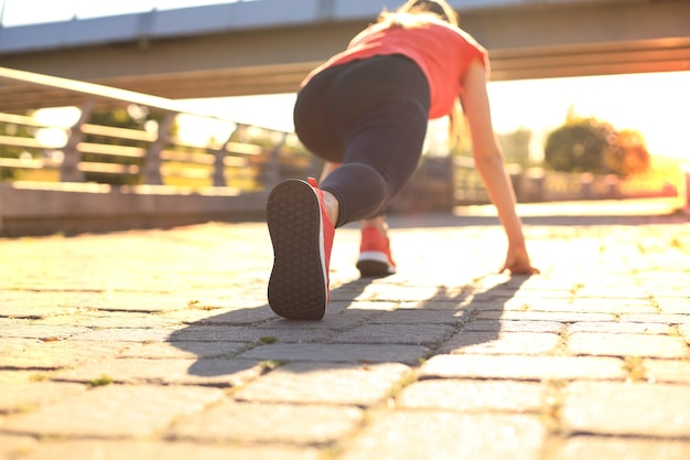 야외에서 달리는 동안 출발선에 서 있는 스포츠 의류를 입은 젊은 여성의 후면.