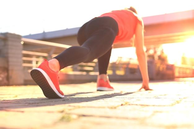 Вид сверху сзади молодой женщины в спортивной одежде, стоя на стартовой линии во время бега на открытом воздухе.