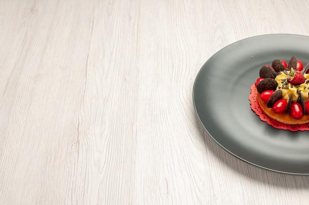 Torta al cioccolato con vista laterale in alto a destra arrotondata con corniolo e lampone al centro nel piatto grigio su fondo di legno bianco