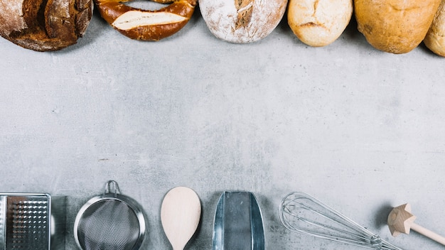 Top row of breads and baking utensil equipments on grunge white background